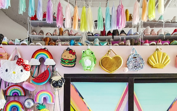 A collection of colourful bags and shoes on a wall.