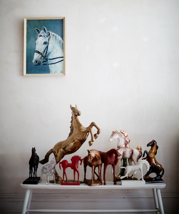 A collection of horse ornaments on a white bench and a painting of a horse on the wall above.