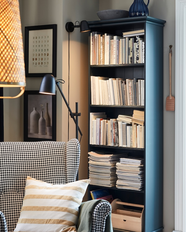 A cosy reading corner with a SKURUP wall lamp, a SKURUP floor lamp, a wing chair and a bookcase in dark blue-green.