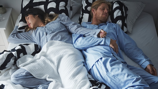 A couple sprawl across a double bed with black and white SKUGGBRÄCKA bed linen and a VÅRELD bedspread, deep in sleep.