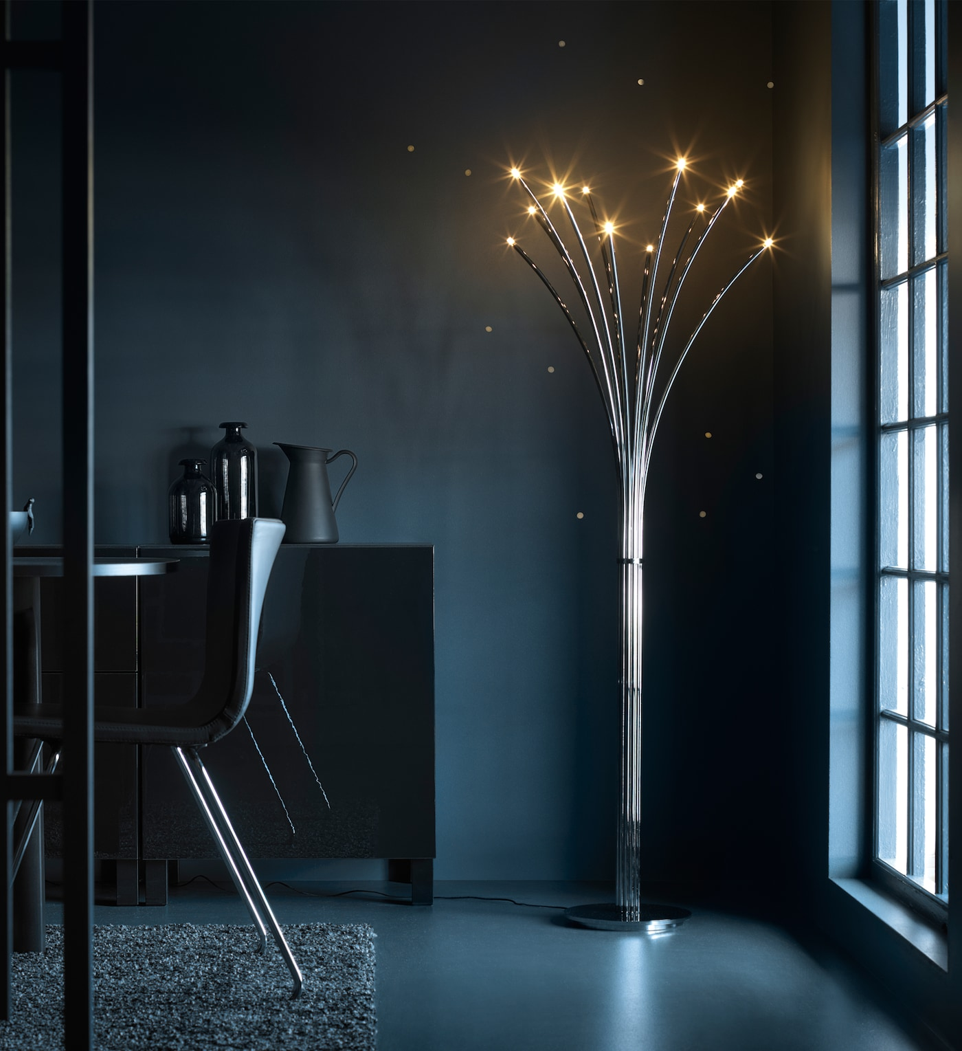 A dark dining room with a lit floor lamp in the corner. The floor lamp has a stainless steel base and at the top sparkling LED lights that looks like fireflies.