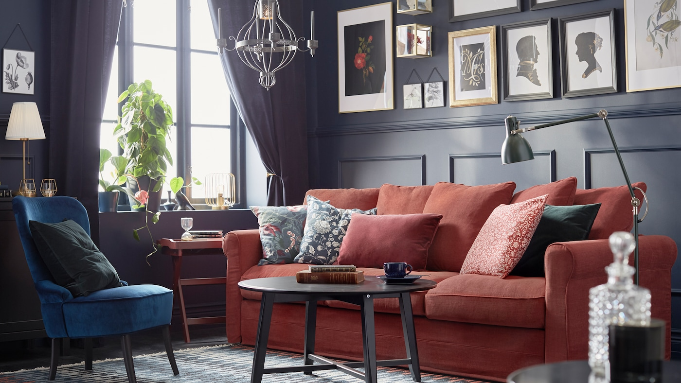 A dark-panelled, traditionally styled room with framed art, a red GRÖNLID sofa with cushions and a KRAGSTA coffee table.
