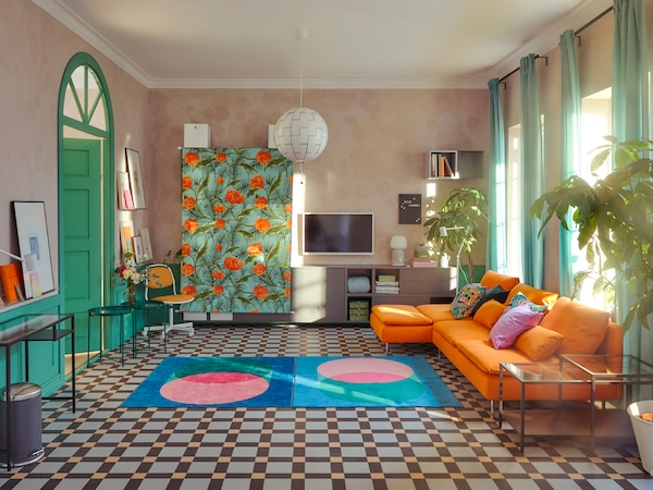 A daytime living room where SÖDERHAMN sofas and other furniture have been either moved to the walls or covered with fabric.