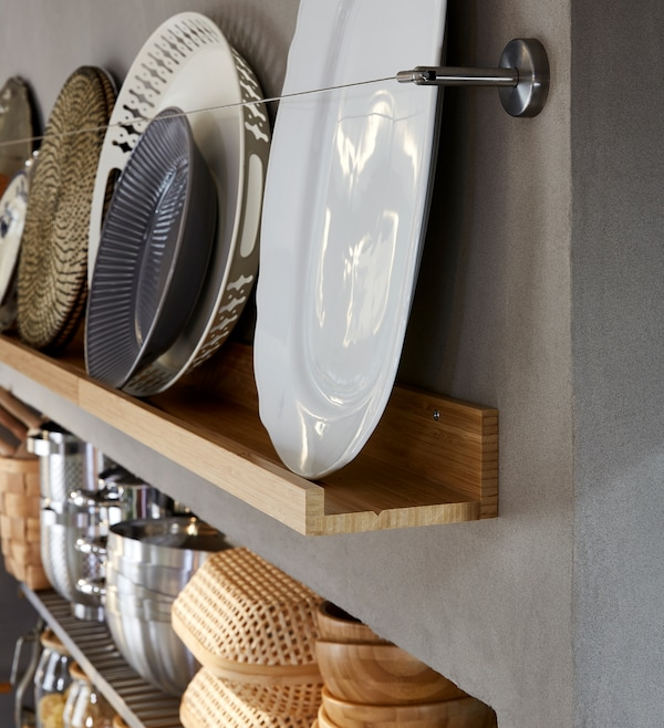 A decorative storage wall with a wooden picture ledge displaying dishes and trays, all in white, grey and brownish tones.