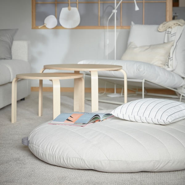 A DIHULT pouffe with handle is lying on a living room rug, and it offers a comfy and spacious seat for children.