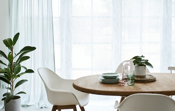 A dining room with a round, wood table and white chairs, in front of French windows dressed with green and white curtains.