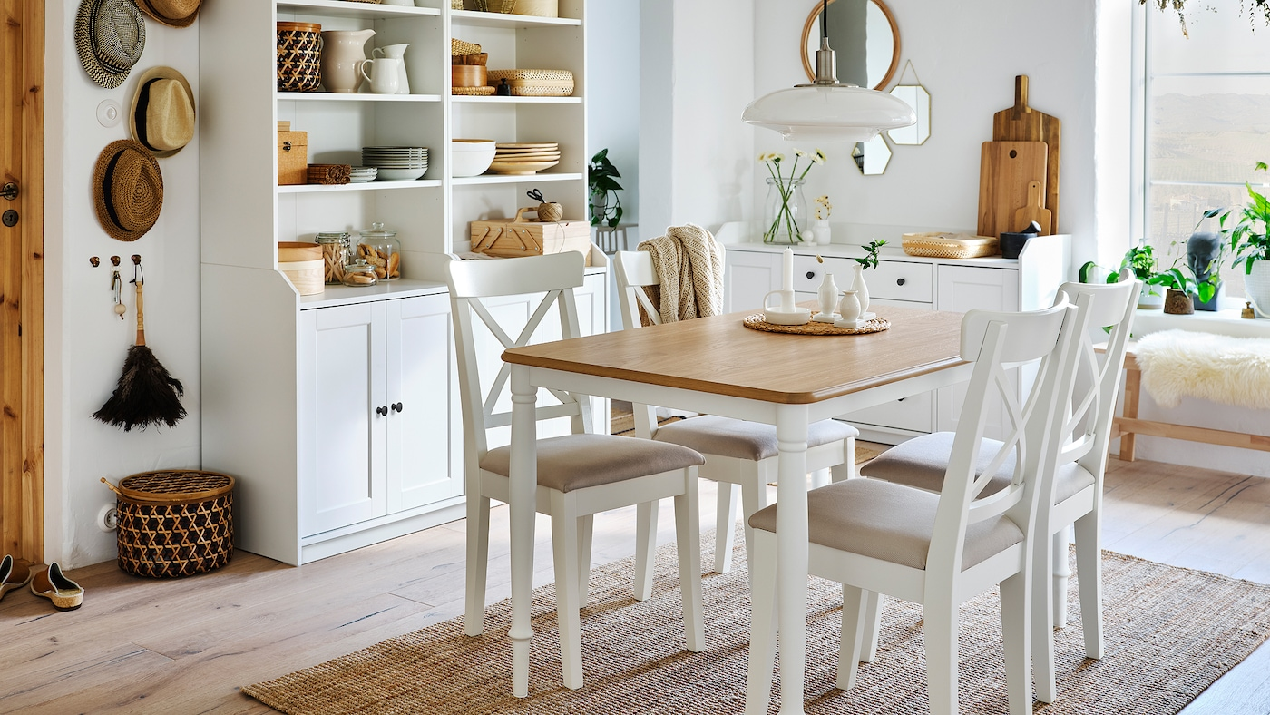 A dining room with a table in oak/white, four white chairs, a jute rug and two white high cabinets with two doors each.