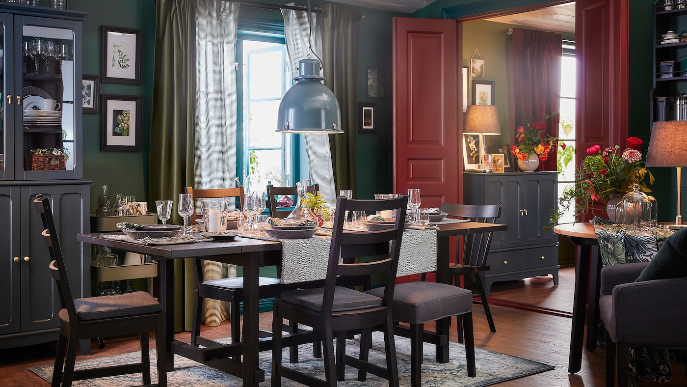A dining room with an table and five chairs in black, an oriental-patterned rug and a grey-turquoise pendant lamp.