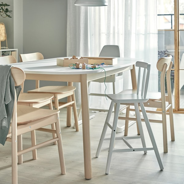 A dining table, chairs in birch, a highchair and a junior chair with feet support. Children's crafts lie on the table.