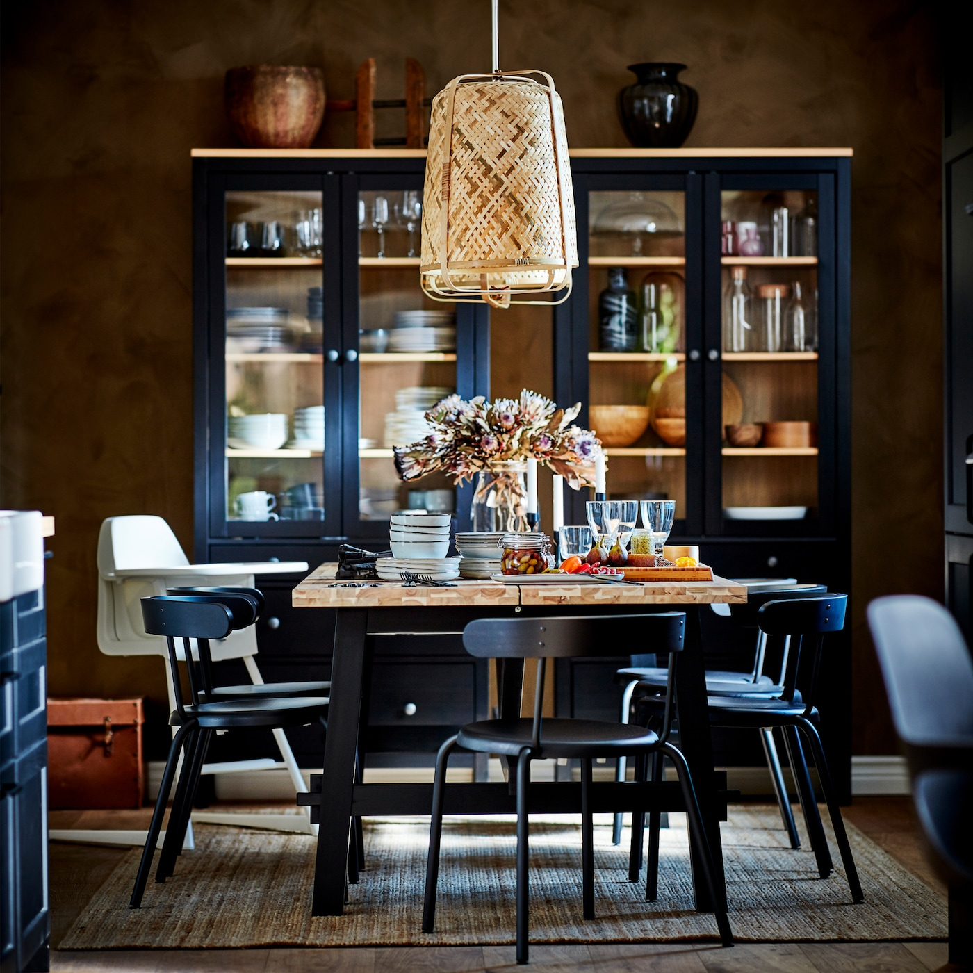 A dining table in black/acacia, anthracite chairs, a jute rug, pendant lamps in bamboo and two cabinets in solid pine.