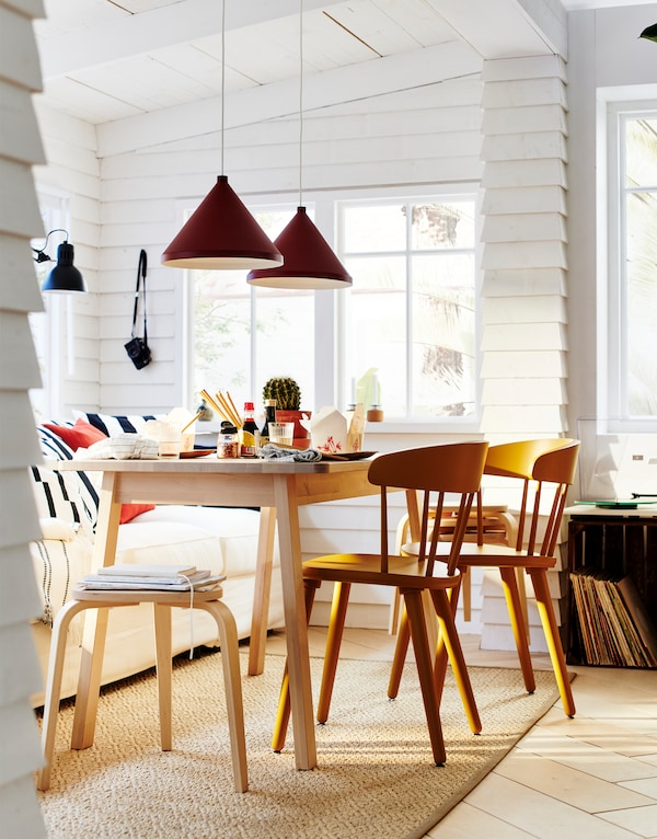A dinner area with a white sofa with pillows and a dining table with several KYRRE stackable stools in birch wood.