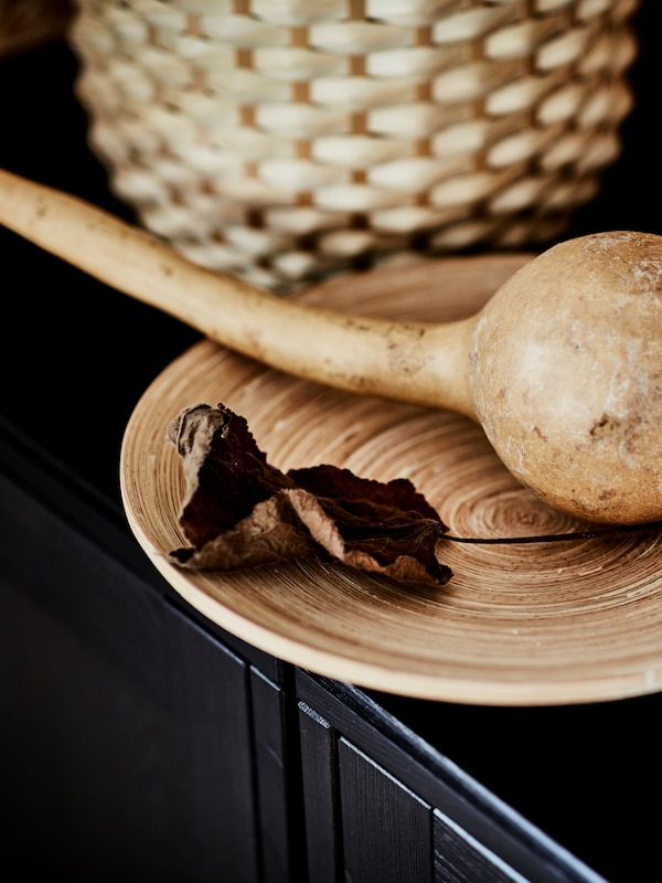 A dried gourd lying together with a withered leaf on a HULTET bamboo dish, in turn placed on a dark, wooden surface.