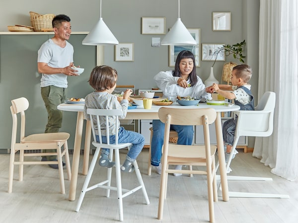 A family in a dining room. The mother and two children sit by the dining table, and the father brings a bowl to the table.
