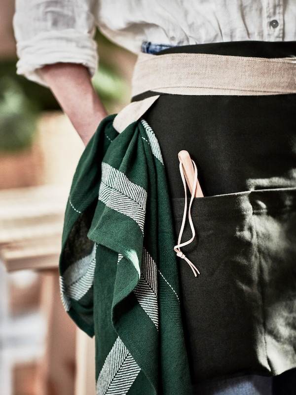 A female urban gardener dressed in a green apron, handmade in natural jute and cotton.