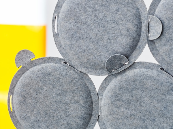 A few circular ODDLAUG sound absorbing panels made in grey felt attached together to absorb annoying sounds.