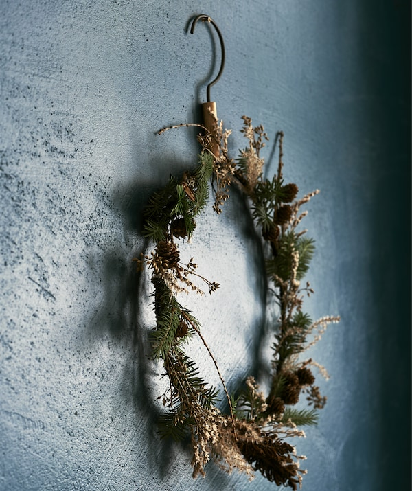 A floral wreath hanging on a blue wall.