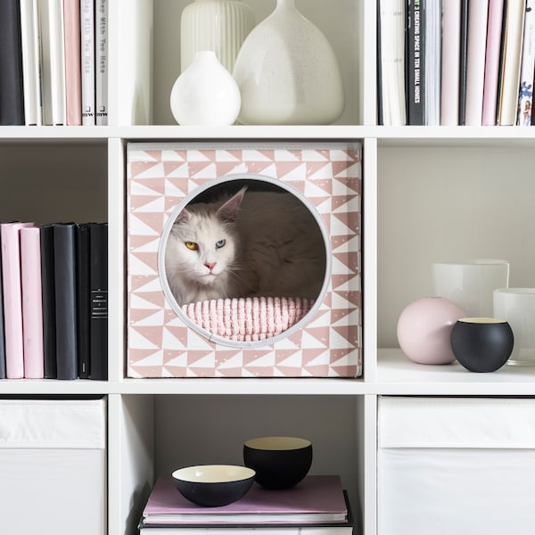 A fluffy white cat relaxes inside a pink LURVIG cat house which is inserted into a KALLAX shelf.