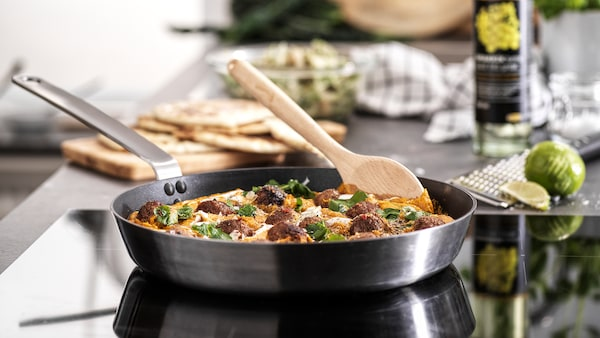 A frying pan with a handle in stainless steel is standing on a hob cooking meatballs in sauce. A wooden spoon is on the side.