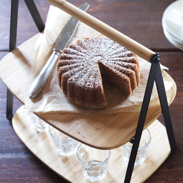 A FULLSPÄCKAD bamboo serving tray with handle, with a cake on the upper layer, and glasses below.