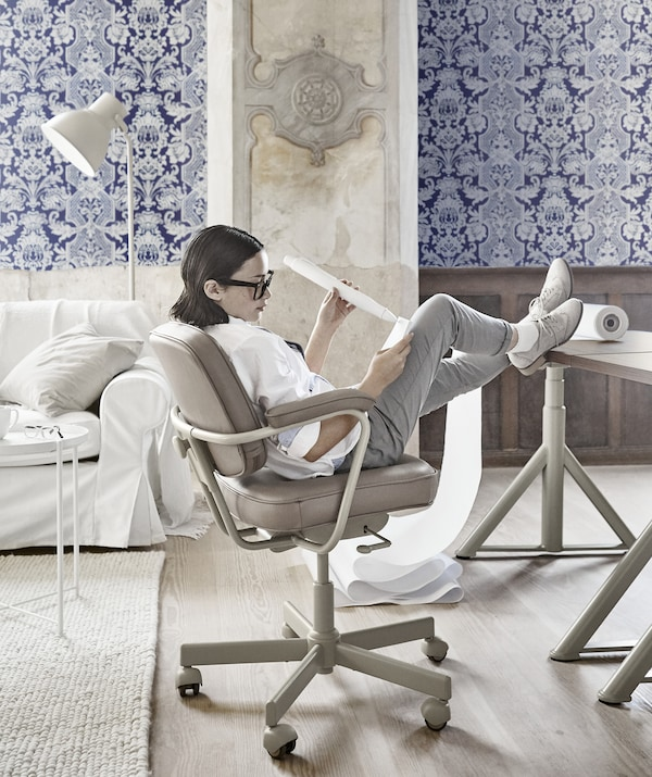 A girl leaning back in a beige swivel chair with her feet up on a desk in an office with blue patterned wallpaper.