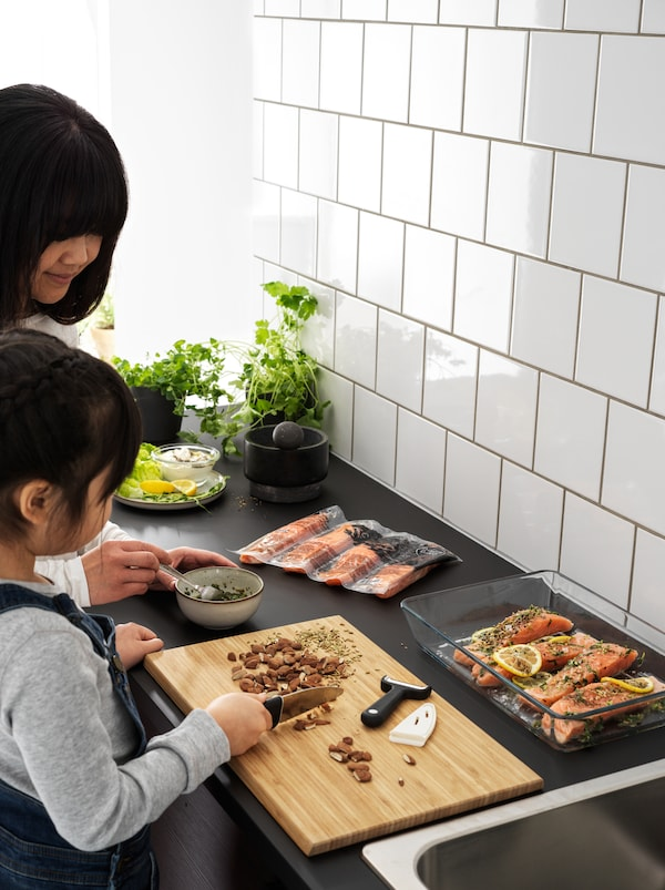 A girl uses a SMÅBIT knife to chop almonds by a black kitchen worktop, assisting her mother in preparing a salmon dish.