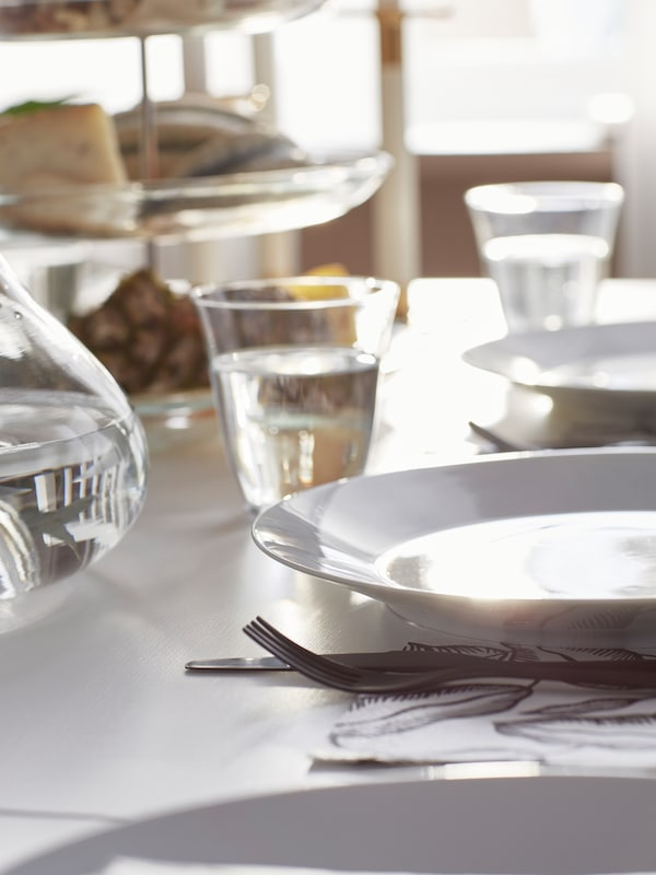 A GLADELIG grey side plate with a stainless-steel knife and fork and a clear drinking glass standing on a set table.