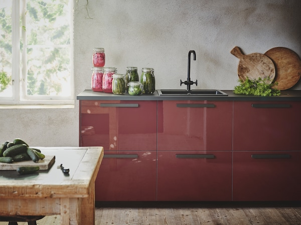 A glossy dark red-brown kitchen with black countertops, handles and sink, stands in a rustic looking room with grey textured walls.