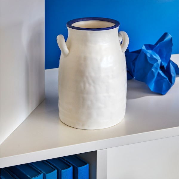 A GODTAGBAR vase designed in the shape of a vintage milk jug, made in stoneware hand-painted in white and blue.