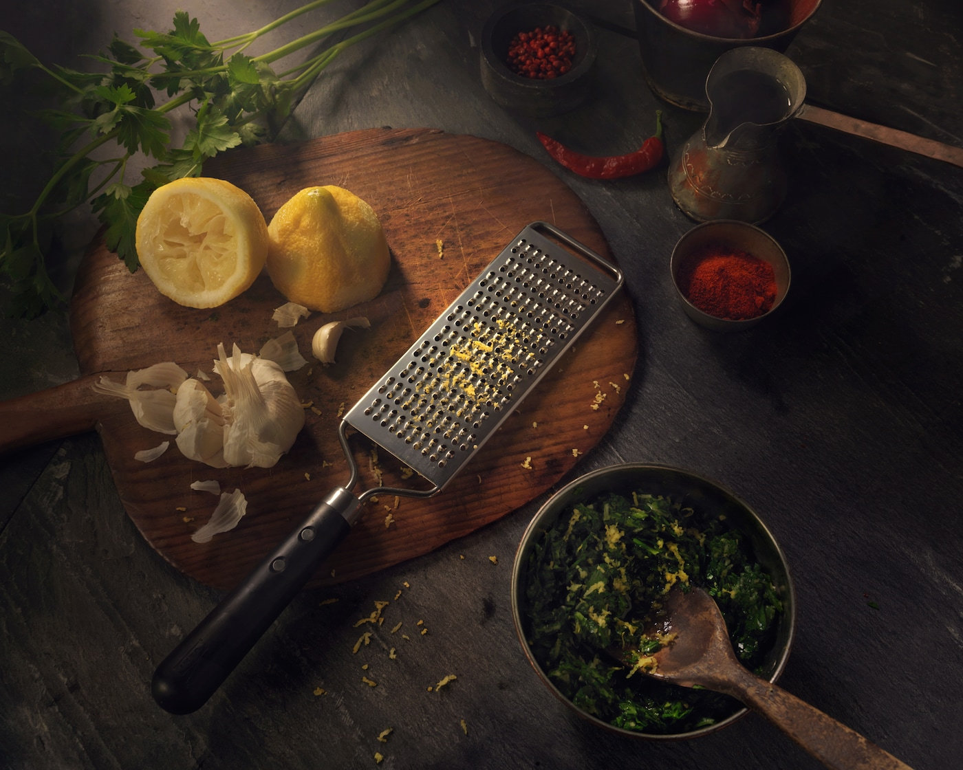 A grater in stainless steel with a black plastic handle. Shown together with a lemon on a wooden chopping board.