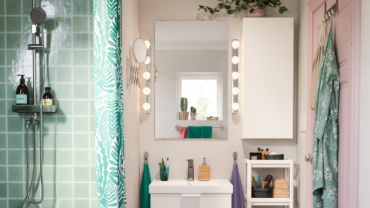 A green tiled shower next to a pink room with a white wash-basin and wall cabinet. Two illuminated LEDSJÖ wall lamps.