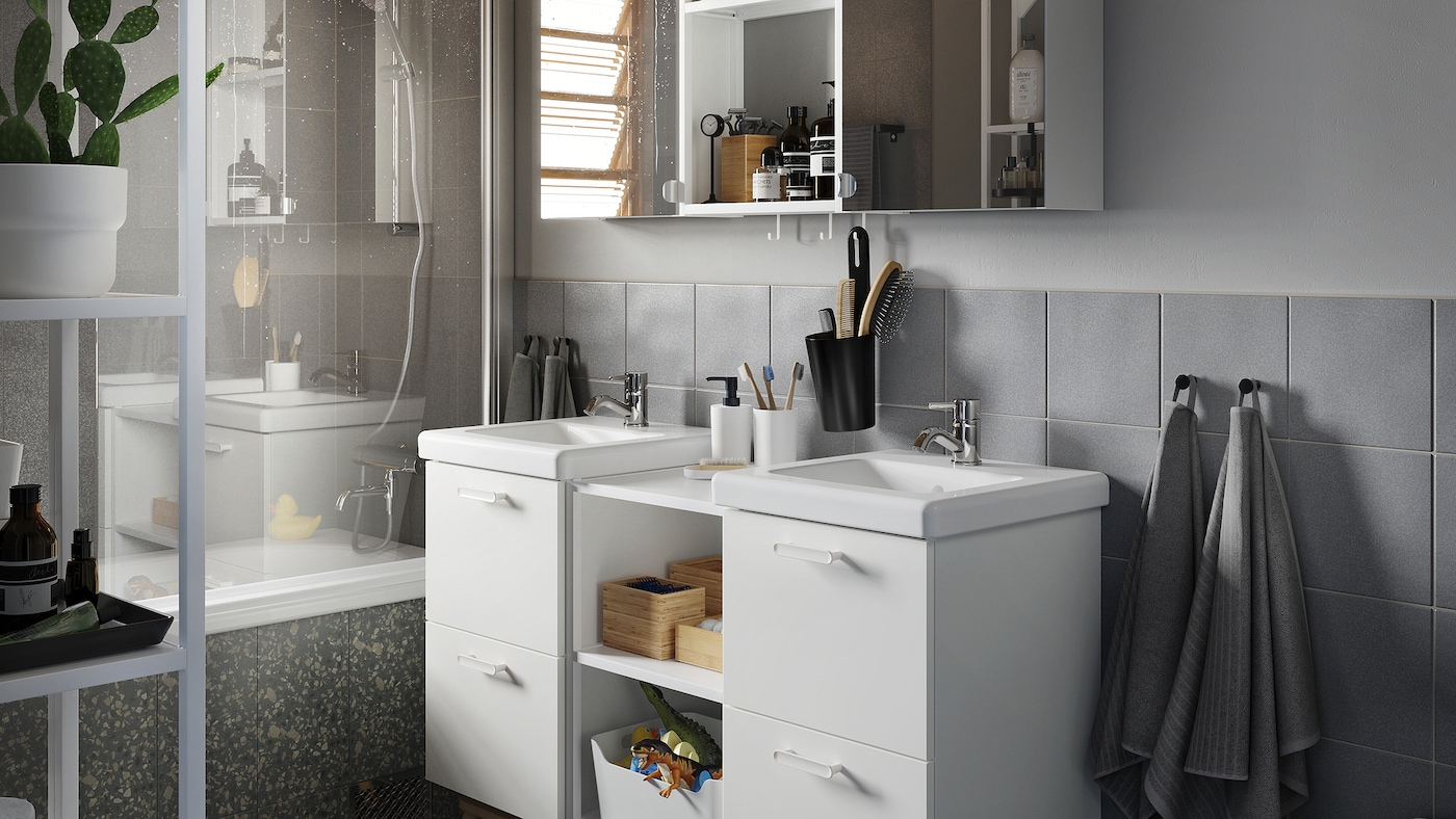 A grey bathroom with wash-stands and wash-basins in white, a cabinet with mirror doors and bamboo accessories.