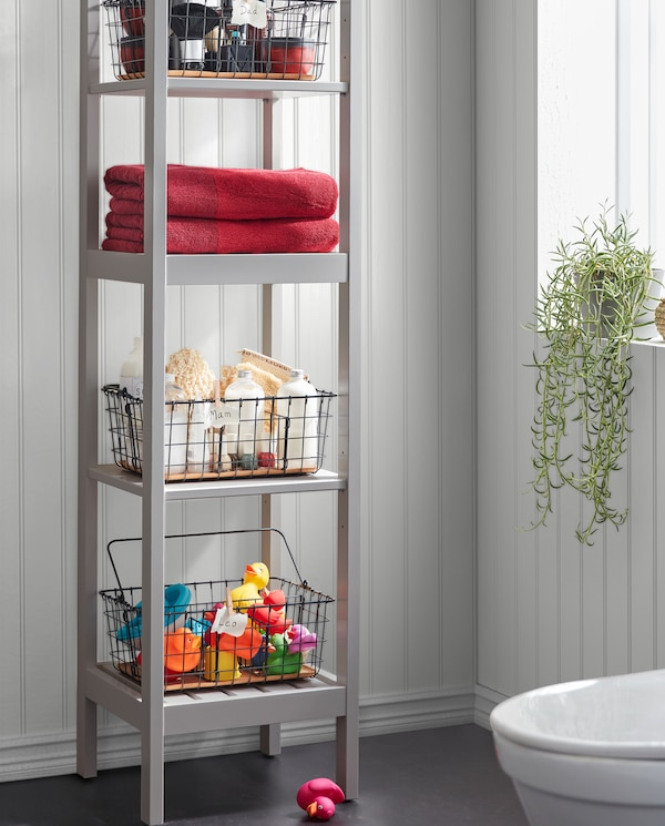 A grey HEMNES shelving unit with black PLEJA wire baskets storing towels, bath toys, spa stuff and more on the four shelves.