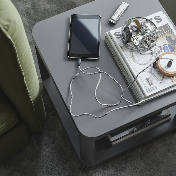 A grey side table, a mesh bowl with keys and a smartphone that's being charged with LILLHULT cable with a textile surface.
