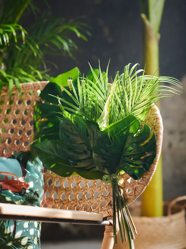 A GRÖNADAL handwoven-rattan rocking chair decorated with a tied-together bunch of SMYCKA artificial leaves.