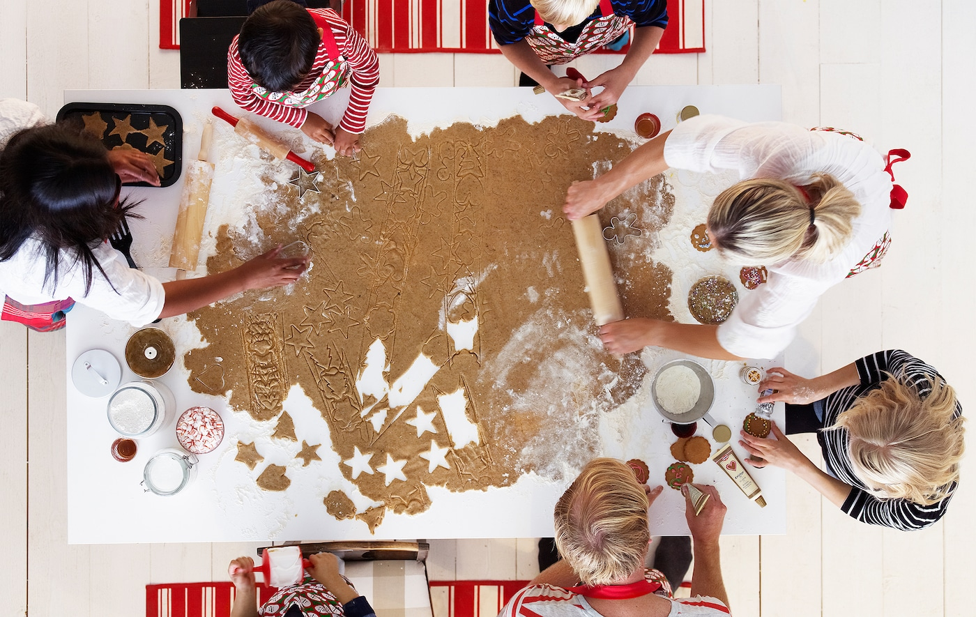 A group of children and adults amid gingerbread baking centred around a very large sheet of dough on a kitchen table.