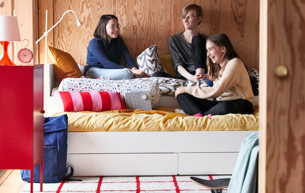 A group of teenage friends chat while sitting together on an extendable SLÄKT bed in a wood-panelled bedroom.