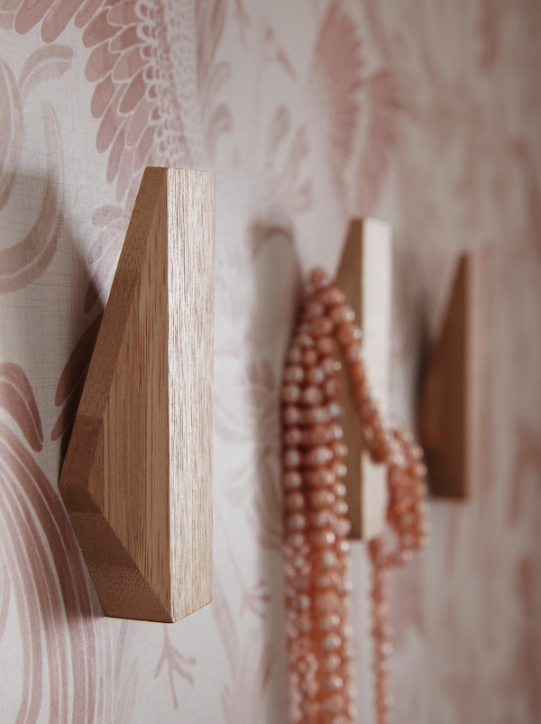 A hallway wall with three SKUGGIS geometrically shaped wooden hooks and a necklace hanging on one of them.