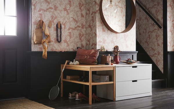 A hallway with a light grey NORDLI chest of two drawers under a round mirror and beside a wooden bench with open shelves.