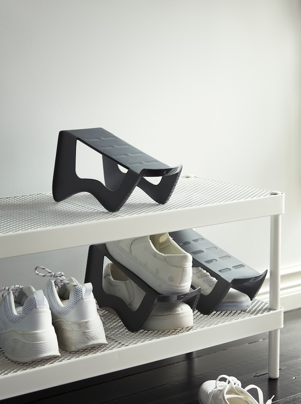 A hallway with a white shoe rack with two mesh shelves and three grey space-saving MURVEL shoe organisers in plastic.