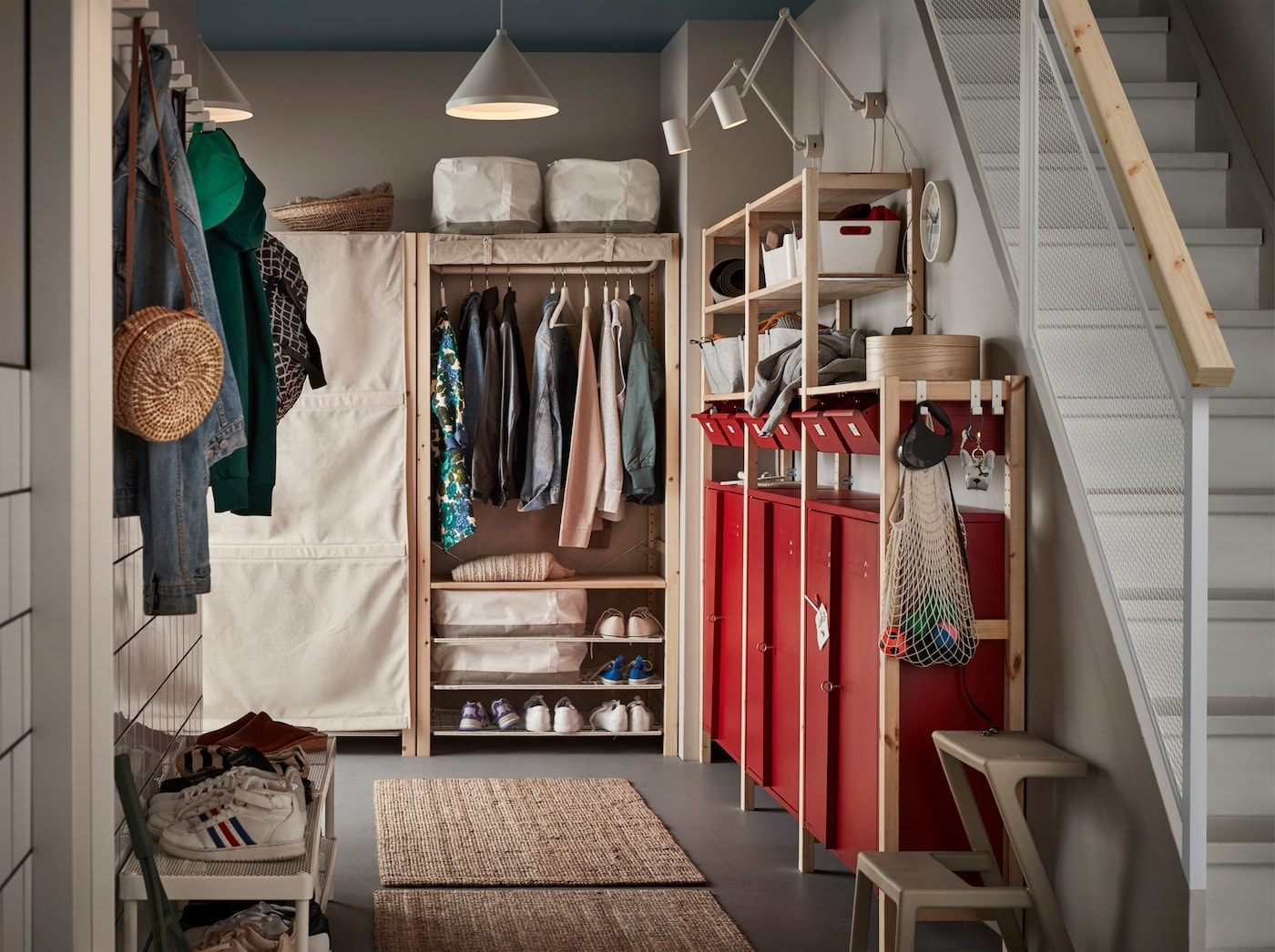 A hallway with red cabinets, white lamps, two jute rugs, white shoe racks and shelving units in beige and pine.