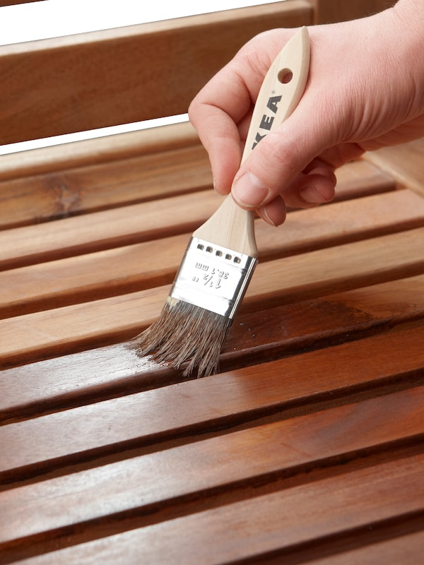 A hand holding a paint brush, painting the wooden slats on a piece of outdoor furniture with stain.
