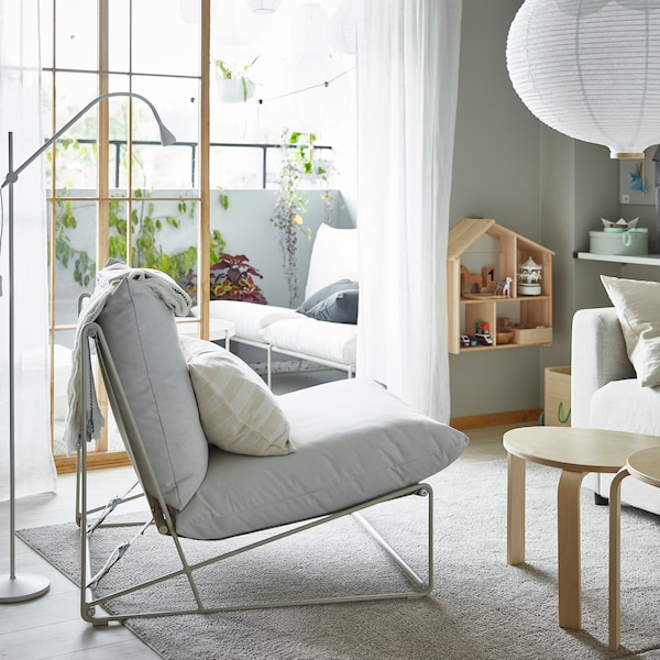 A HAVSTEN easy chair in a living room and HAVSTA 2-seat sofa on a balcony – they can be used both indoors and outdoors.