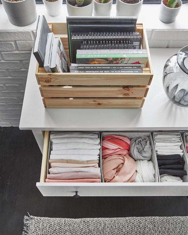 A HEMNES white chest of 3 drawers has one drawer that is open where folded clothes are organised inside boxes.