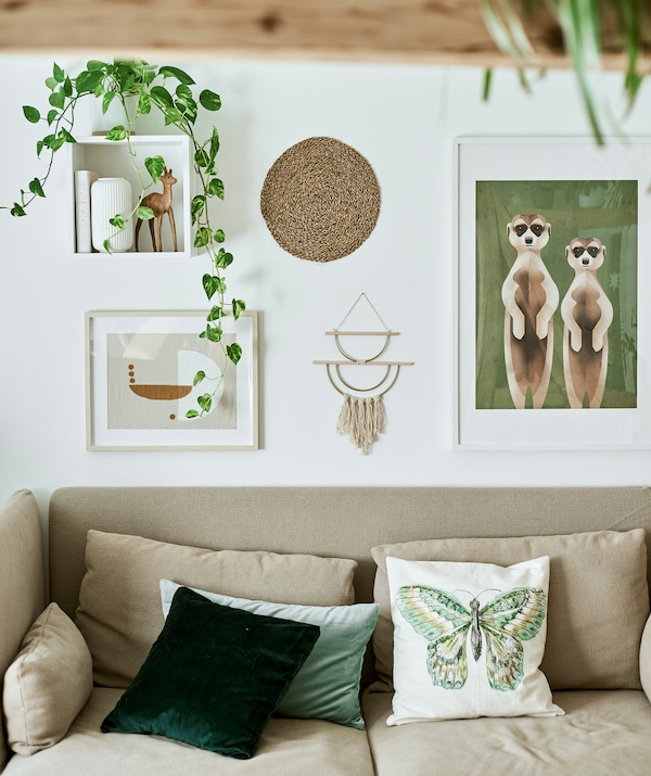 A high-backed sofa with green cushions against a white wall with a display of framed illustrations, wall hangings and plants.