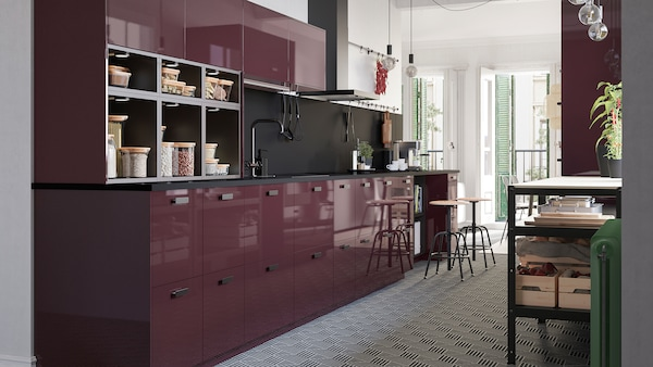 A high-gloss kitchen in burgundy, a hexagon-patterned floor and naked light bulbs on cords that hang from the ceiling.