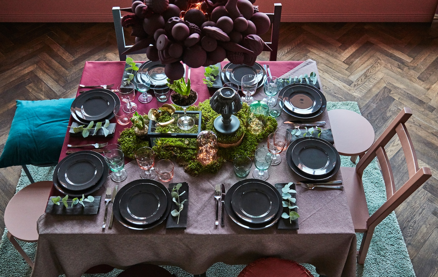 A holiday table is set using dark reds and greens, and greenery.
