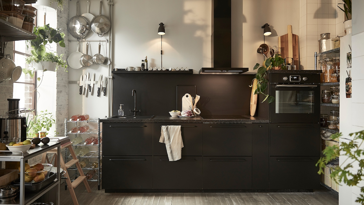 A kitchen area with black IKEA KUNGSBACKA kitchen cabinet doors, a stainless steel trolley and two black wall lamps.