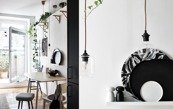A kitchen table with plants on a shelf above, and a close-up of monochrome trays on a shelf and filament bulbs.