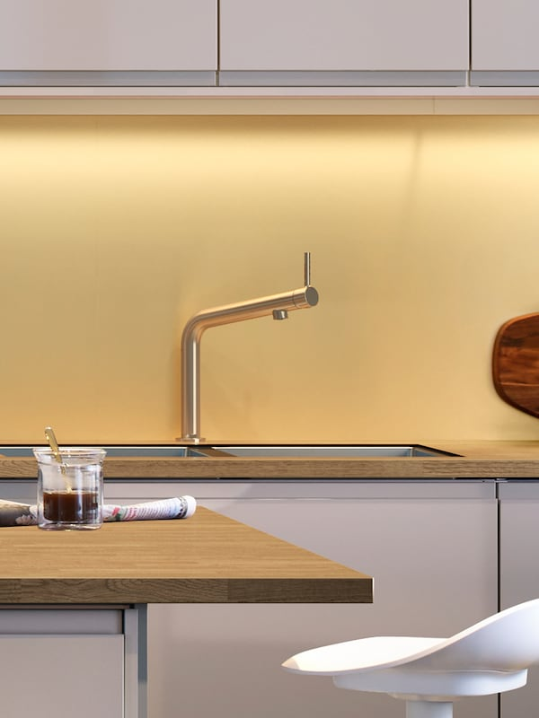 A kitchen with a yellow wall panel, a stainless steel mixer tap and a wooden worktop with a kitchen island in front.
