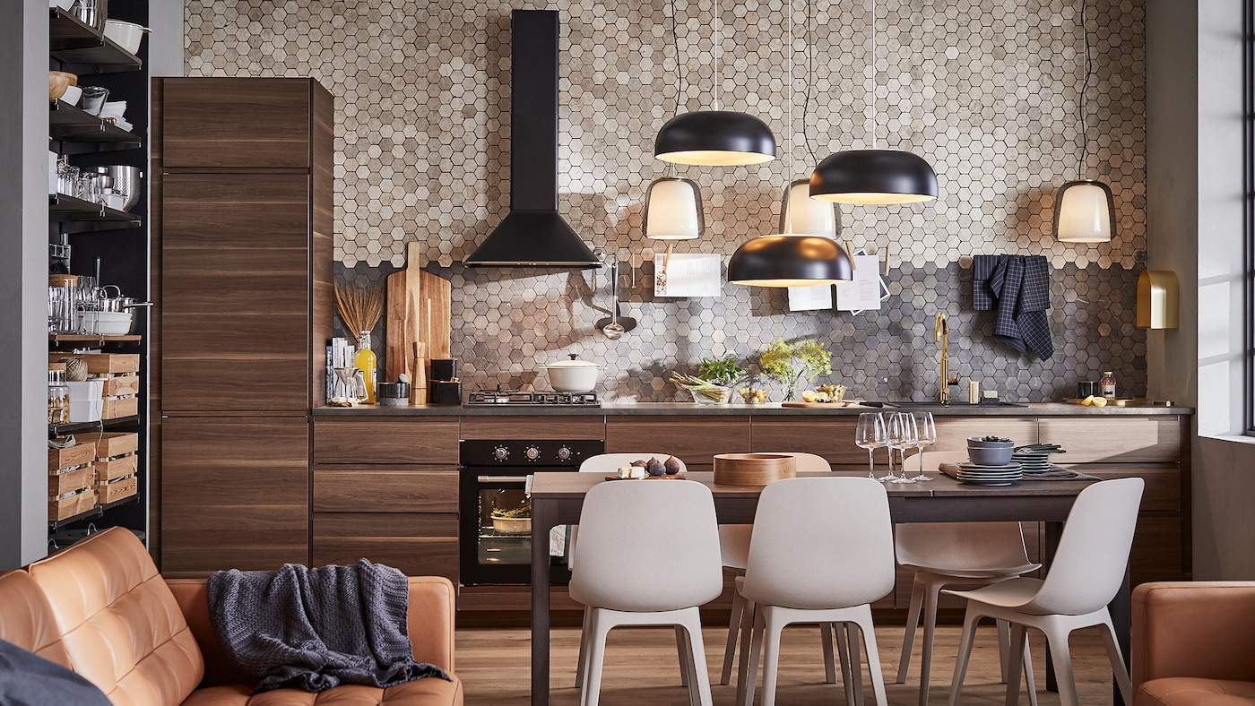 A kitchen with cabinets in dark brown walnut-effect wood, three black pendant lamps, a dark brown table and six chairs.